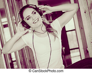 Woman with headphones listen music and dance.
