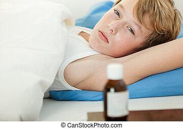 Feverish boy in bed next to medicine bottle - Feverish boy...