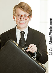 Smiling boy in business suit holding brief case wearing...