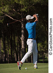golf player hitting shot with club on course at beautiful...