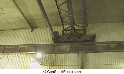 Electric hoist moves slowly under roof of plant. It is a...