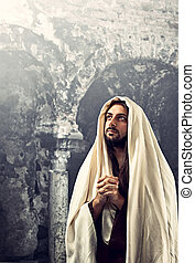 Jesus Christ prays with clasped hands turning our gaze to...