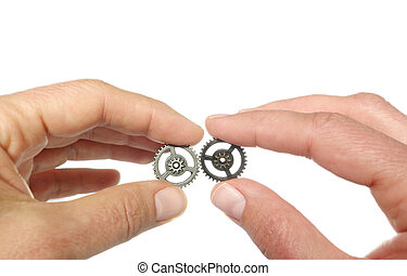 Two gears together - Two hands placing gears together,...