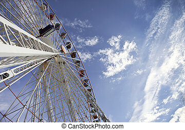 Big wheel in a fairground - Big wheel and cloudy blue sky in...