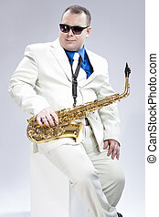 Music Concept. Portrait of Handsome Caucasian Musician With Alto Saxophone Posing In White Suit Against White Background. Wearing Black Sunglasses.