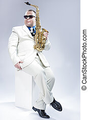 Music Concept. Full Length Portrait of Expressive Caucasian Musician With Alto Saxophone Posing In White Suit Against White Background. Wearing Black Sunglasses