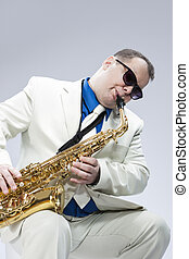 Caucasian Mature Male Musician Playing Alto Saxophone and...