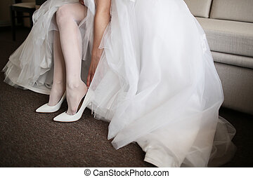 Beautiful bride in white wedding dress is holding shoes in...