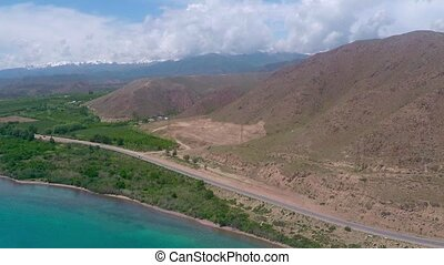 Aerial video of rural road along mountainous sea shore on...