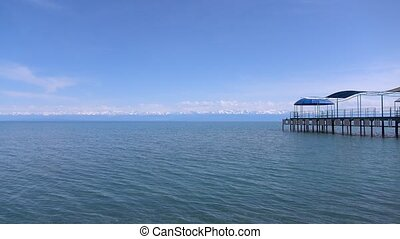 Empty pier, lake and distant snow peaks on the horizon. 4K...