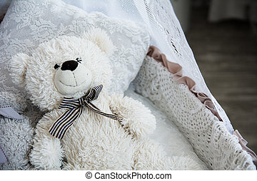 Childrens cot with a teddy bear on a background of a brick...