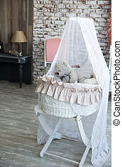 Children wicker cradle with teddy bears on the brick wall...