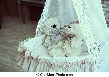 Baby cot with teddy bears on a background of a brick wall...