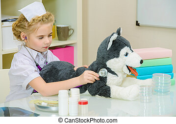 veterinarian - Cute little girl playing a doctor at home....