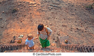 climb the stairs to the temple - young woman with toddler...