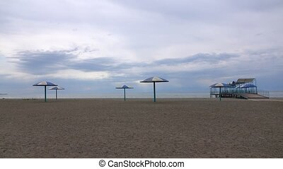 Empty sandy beach and big sun umbrellas on a cloudy day. 4K...