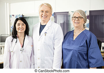 Confident Medical Team Standing Together In Clinic -...