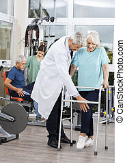 Senior Woman Using Walker While Assisted By Male Doctor