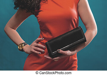 Fashionable woman in red evening dress with a black handbag