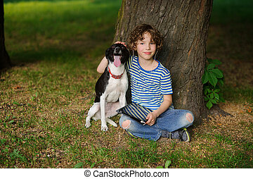 Boy with dog sits on the earth under a tree. - The boy with...