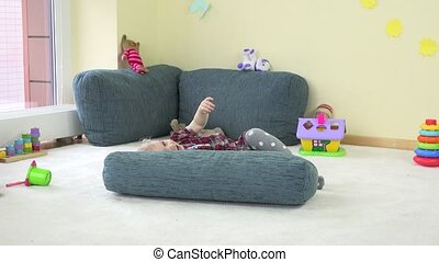 cheerful toddler boy hide under blue big pillow and show...