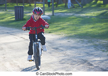 Child riding his mountain bike - Child with a helmet riding...