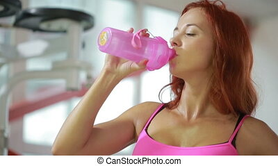 sportive female thirsty after active workout, drinking fresh water
