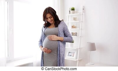 happy pregnant woman with big tummy at home - pregnancy,...