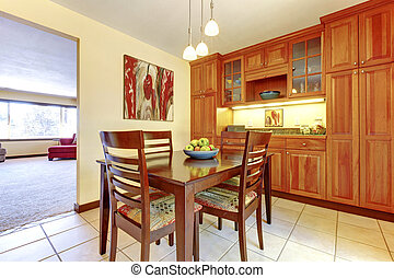 Bright orange wood kitchen and dining room with tile floor.