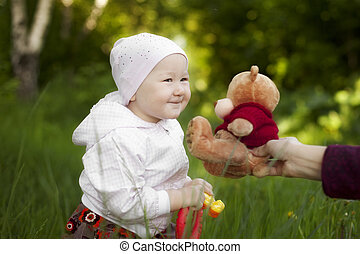 little girl summer happy Teddy bear, which gives her mom