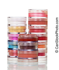 Set of bright eye shadow in transparent jars on white.