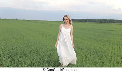 Young Woman Walking Through Summer Field, Rear View