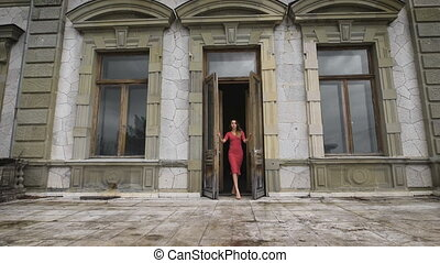 Attractive girl in red dress goes on the balcony of an old manor.