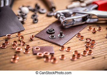 Eyelet punch and rivets for leather on wooden background