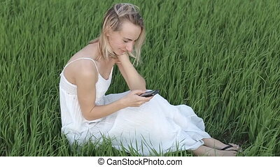 woman types message lying down in the park: smartphone:...