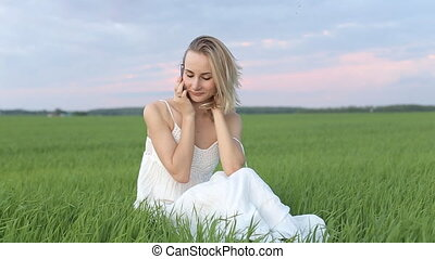 Cute young woman speaking on a mobile phone on the grass