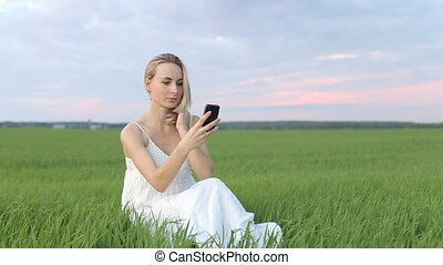 Blonde girl doing SELF phone in the grass