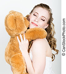 young beautiful bride holding a teddy bear, they gently hug