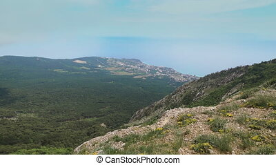 Panoramic view from the mountains to the sea, forest and settlements.