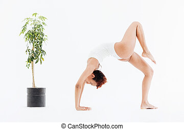 Attractive african american flexible woman doing backbend...