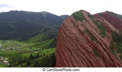 Striped orange rocks, green hills, snowy peaks and valley village aerial video
