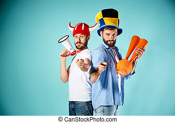 The two football fans with mouthpiece over blue background