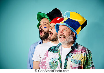 The three football fans singing the national anthem over...