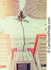 Beautiful beach chairs with umbrella around outdoor swimming pool neary sand and sea