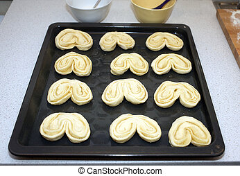 Preparing for baking small buns from dough Twelve puffs on...
