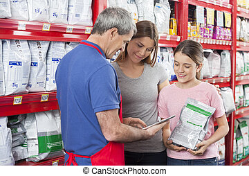 Salesman Using Digital Tablet While Assisting Family In Pet...