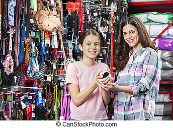 Happy Mother And Daughter With Guinea Pig In Pet Store -...
