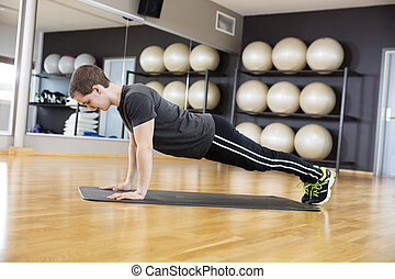 Side View Of Man Performing Pushups On Mat In Gym