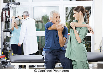 Nurse Guiding Senior Man In Stretching Exercise At Rehab...