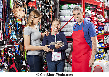 Cute Girl Holding Rabbit With Mother And Salesman In Shop -...
